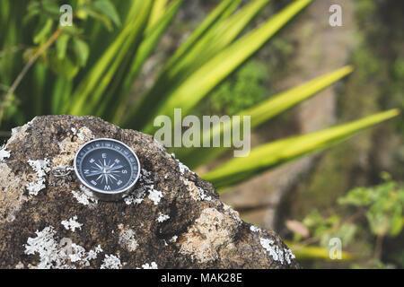 Navigation concept - Analogical compass laying on the rocky stone. Agave plant leaves in background - Stock Photo
