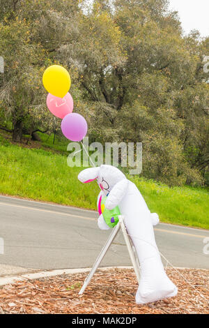 A large stuffed white Easter bunny is draped over an open house real estate sign with three multicolor ballons tied to strings floating above it by a  - Stock Photo