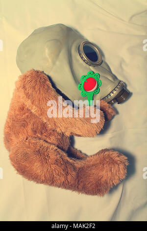 A toy in a gas mask as a concept for protecting children from the use of gas weapons, environmental pollution and the International Day of Remembrance - Stock Photo