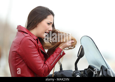 Portrait of a sad biker woman complaining about tangled hair after a motorkike travel - Stock Photo