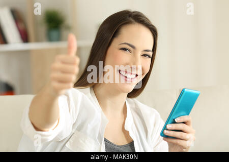 Satisfied girl holding a smart phone gesturing thumbs up sitting on a couch in the living room at home - Stock Photo