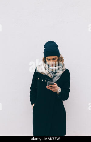 Beautiful hipster girl uses smart phone standing outdoors near wall in cold season. Vertical photo stylish dressed woman holding cellphone on solid gr - Stock Photo