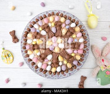 Looking down from above onto an Easter celebration cake decorated in mini easter eggs and chocolate candy on a white background - Stock Photo
