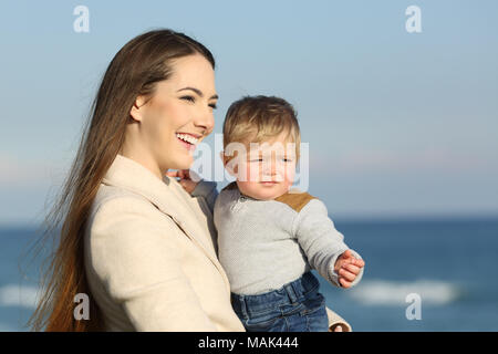Happy mother and serious kid son looking away outdoors on the beach - Stock Photo