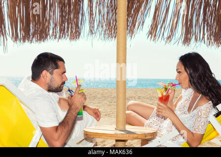 Cute young couple lying on deckchairs on the beach with cocktails. - Stock Photo