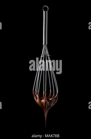 Whisk with melted chocolate cream isolated on black background - Stock Photo