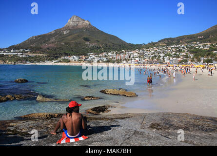 Black man sitting on the rocks by the sandy, white beaches of upmarket Camps Bay, with the Lion's Head beyond, in Cape Town, South Africa - Stock Photo