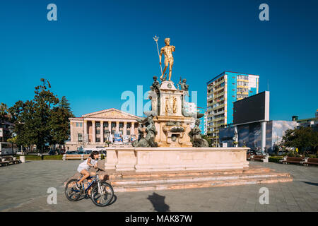 Batumi, Adjara, Georgia - September 10, 2017: Girl Riding On Bike Near Neptune Fountain In Park On Rustaveli Ave. Famous Landmark. - Stock Photo