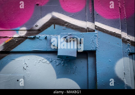 close up of a padlock on a spray painted door, graffiti. - Stock Photo