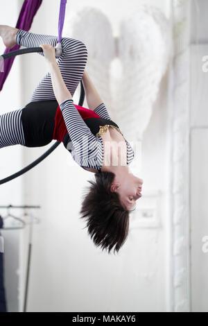 Flexible woman gymnast hangs upside down on the aerial hoop - Stock Photo