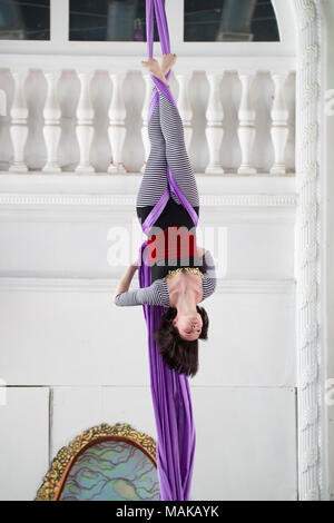 Attractive air gymnast hangs upside down performing an beautiful elements on the aerial silk - Stock Photo