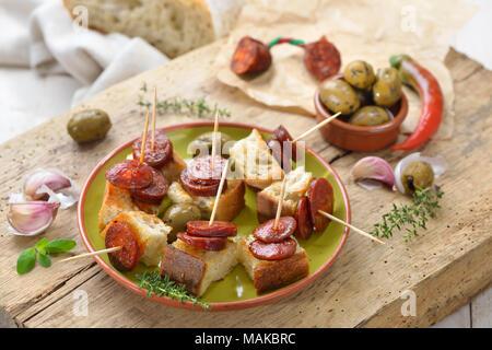 Spanish pinchos: Fried spicy chorizo sausage on roasted bread - Stock Photo