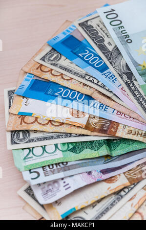 A lot of banknotes of different countries of the world, the difference in value stacked on the table. - Stock Photo