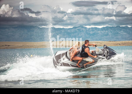 Young couple on Jet Ski, Adriatic sea, Croatia. Summer heat, active sport, recreation, vacation and fun on the beach. - Stock Photo
