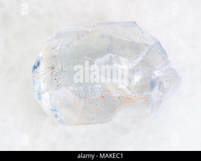 macro shooting of natural mineral rock specimen - raw crystal of celestine stone on white marble background from Arkhangelsk region of Russia - Stock Photo
