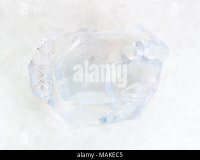 macro shooting of natural mineral rock specimen - rough crystal of celestine stone on white marble background from Arkhangelsk region of Russia - Stock Photo
