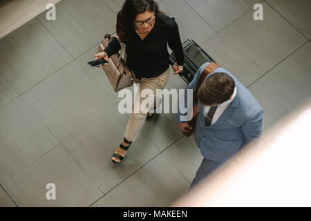 Top view of two business travelers walking together with luggage and chatting. Business people arriving for a conference. - Stock Photo
