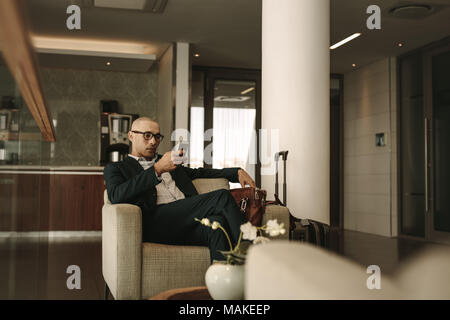 Business traveler waiting in airport lounge and using mobile phone. Businessman waiting for fight at airport lounge. - Stock Photo