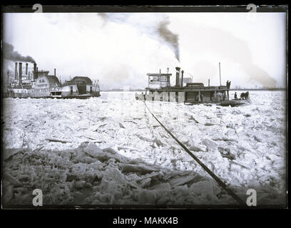 Horizontal, black and white photograph showing steamboats caught on an icy river, possibly during the ice gorge of 1887. The steamboat John Trendley, owned by the Wiggins Ferry Company, is on the left, with an unidentified steamboat behind it. These steamboats appear to be trapped in the ice. On the right, there is a boat named Rescue No. 2, with a rope running from the boat's deck into the foreground. Several men are standing on the boat's deck, using poles or other long tools. The path in front of Rescue No. 2 appears blocked by ice, and there are ice chunks throughout the foreground. Title: - Stock Photo