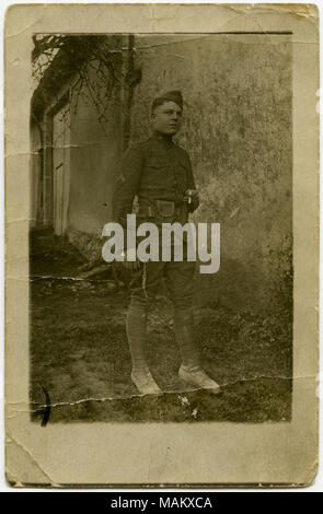 Vertical, sepia postcard showing a man in military uniform posing for a picture in front of a concrete wall, possibly part of a house or other building. The man is holding a cigarette in his left hand. A note written on the back of the postcard reads: 'Not very good, but I guess you know who it is.' The postcard might be of French origin. Title: Uniformed Soldier Posing in Front of a Concrete Wall for a Picture.  . between circa 1916 and circa 1918. - Stock Photo
