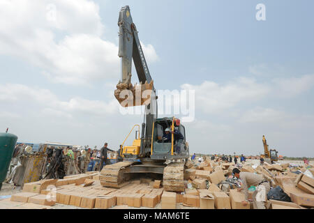 Phnom Penh. 3rd Apr, 2018. An excavator crushes the boxes of counterfeit cosmetics on April 3, 2018 in Phnom Penh, Cambodia. Cambodian authorities on Tuesday destroyed more than 60 tons of counterfeit cosmetics confiscated in recent months, officials said. Credit: Phearum/Xinhua/Alamy Live News - Stock Photo