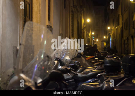 Rome, Italy - November 18, 2017 Motorcycles parked against the wall in the light of street lamps - Stock Photo