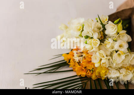 Bouquet of white and yellow freesia on white tabletop. Copy space. Horizontal composition. - Stock Photo