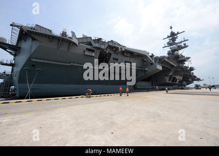 SINGAPORE (April 2, 2018) - The aircraft carrier USS Theodore Roosevelt (CVN-71) moored in Singapore's Changi Naval Base today. Theodore Roosevelt is currently underway for a regularly scheduled deployment in the U.S. 7th Fleet area of operations in support of maritime security operations and theater security cooperation efforts. (U.S. Navy photo by Marc Ayalin/Released) - Stock Photo
