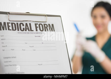 Female medicine doctor hand holding silver pen writing something on clipboard closeup. Medical care, insurance, prescription, paper work or career con - Stock Photo