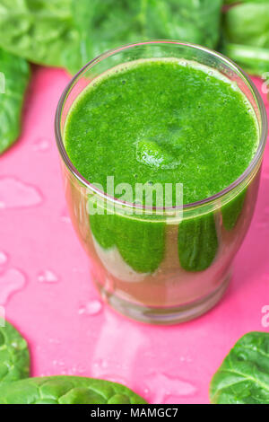 Glass with Green Fresh Smoothie from Leafy Greens Vegetables Fruits. Apples Bananas Kiwi Zucchini Scattered Spinach Leaves on Fuchsia Pink Background  - Stock Photo