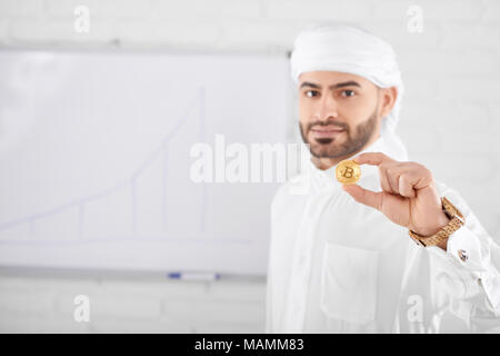 Wealthy handsome muslim male model in traditional Islamic clothing holding golden bitcoin in front of white board wall. Selective focus, blurred background, horizontal shot. Concept of cryptocurrency. - Stock Photo