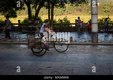 Yangshuo, China - August 1, 2012: Street scene in the town of Yangshuo with a woman and a boy in a bicycle, in China. - Stock Photo