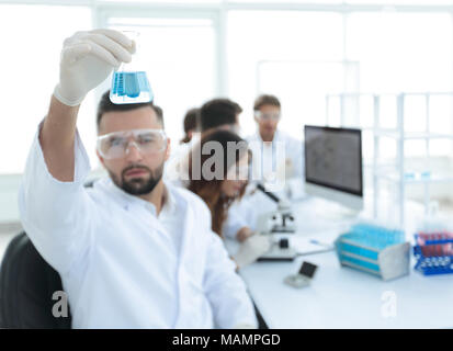 biochemist with flask Petri sitting at a Desk Stock Photo: 210263180 ...