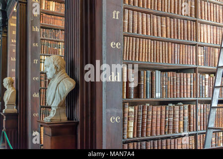 Statues and bookshelves in The Long Room in the Trinity College Old Library in Dublin, Ireland - Stock Photo