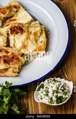 Homemade delicious Turkish style cheese pie in enamel plate on wooden background - Stock Photo