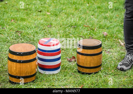 The three bottles (small kegs, two of beer, one empty), unadorned, and on the ground before the start of the annual easter monday contest with the nea - Stock Photo