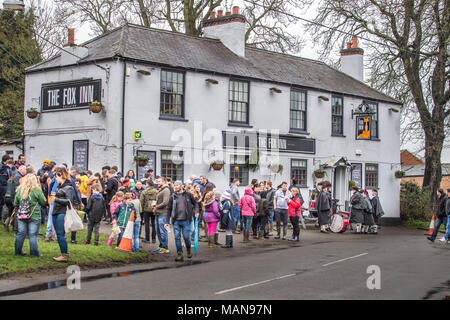 Villagers gather at the Fox inn before the hare pie parade to the local church of St Michael and All Angels for the pie to be blessed by the vicar bef - Stock Photo