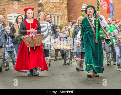 Villagers carry the hare pie in parade to the local church of St Michael and All Angels for the pie to be blessed by the vicar before being broken and - Stock Photo
