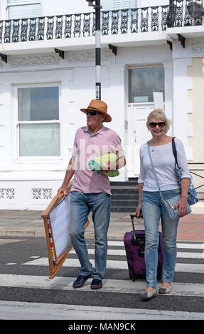 Elderly couple of holidaymakers crossing the road in a holiday resort. - Stock Photo
