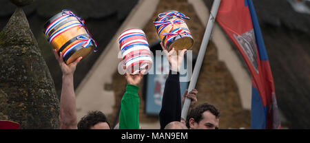The three bottles (small kegs, two of beer, one empty), decorated, and held aloft in the village of Hallaton before the start of the annual easter mon - Stock Photo