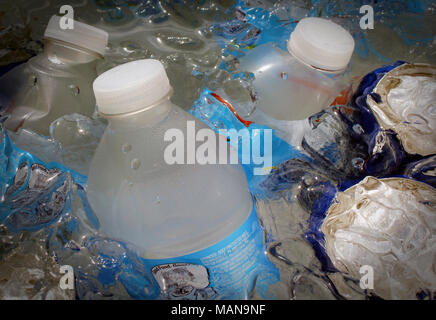 A cooler filled with cold water, ice cubes, water bottles and soda tins. Perfect refreshment on a hot summer day. - Stock Photo