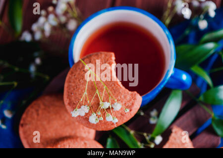 Close-up of a teacup with oatmeal cookies and spring gypsophila flowers on a warm wooden background. Blue ceramic cup on a blue linen napkin. Breakfas - Stock Photo
