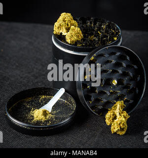 A medicinal marijuana grinder with keef and scraper. Black background - Stock Photo