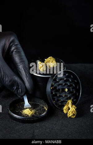A medicinal marijuana grinder with keef and scraper. a hand with a black latex glove holding a fresh nug. Black background - Stock Photo