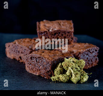 A stack of marijuana edible brownies next to a small pile of medical marijuana nugs. Black background - Stock Photo