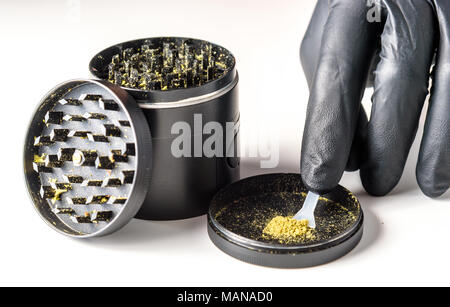 Medicinal marijuana against a white background. Black grinder open with Keef and Keef scraper with a gloved hand gathering keef - Stock Photo