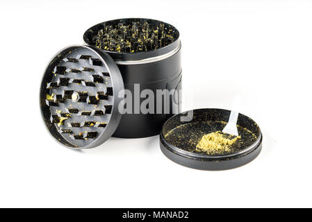 Medicinal marijuana against a white background. Black grinder open with Keef and Keef scraper - Stock Photo
