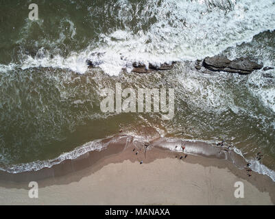 People on ocean coastline in sunny day above aerial drone view - Stock Photo
