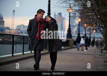 Couple Walking Along South Bank On Winter Visit To London - Stock Photo