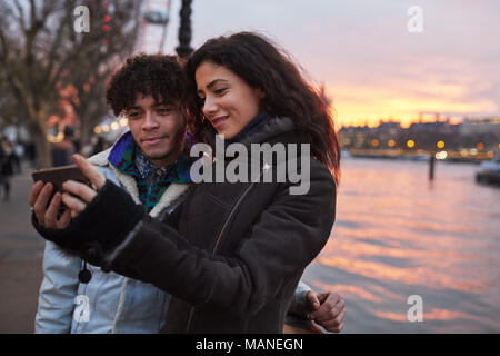 Couple Taking Selfie During Walk Along South Bank In London - Stock Photo